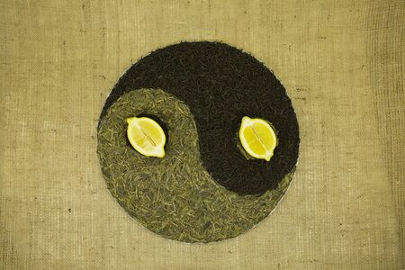 The concept of yin yang. Sign yin yang against the background of burlap. Chinese green tea Lundzyn, Indian black tea and lemon were used.