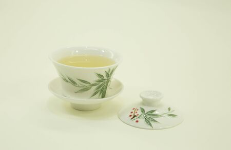 Chinese green tea. Milk Oolong Tea. Green tea in a beautiful traditional oriental cup with saucer. Isolated on a white background.
