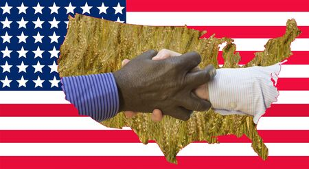 Close up photo of a handshake between afroamerican and european hands. Handshake in front of US flag. On the flag are the contours of the US mills and the wheat field.