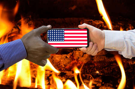 Close up of afroamerican and caucasian white hands holding the phone with US flag in front of a bonfire. America above all.