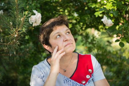 Picture of a middle-aged woman. Concept of emotions. Woman is happy to have rest outdoors after quarantine is relaxed.
