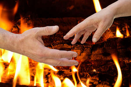 Moments before the touch. Man's and woman's hands in front of bonfire.