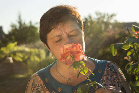 Middle-aged woman and a rose. The woman inhales the aroma of the rose at sunset. The rose shines at sunset.