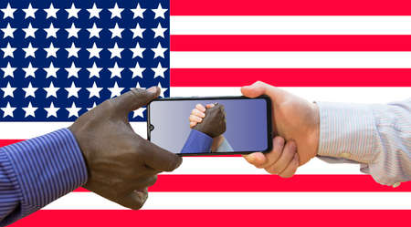 BLM White and afroamerican hands are holding phone with photos of themselves holding US flag. 免版税图像 - 151139631