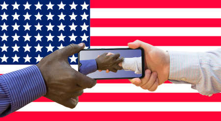 BLM White and afroamerican hands are holding phone with photos of themselves holding US flag. 免版税图像