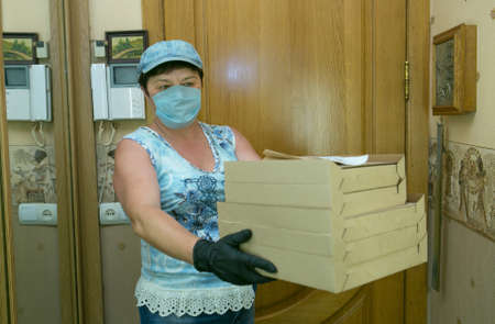 A deliverywoman. A middle-aged woman brought pizza home to a customer. The deliveryman's work in the conditions of coronavirus.