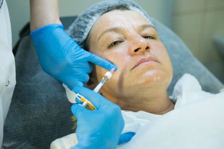 Wrinkle correction procedure. The doctor beautician injects the patient to rage facial wrinkles. Banco de Imagens