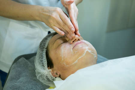 A visit to a beautician. Doctor beautician prepares the patient's face for the procedure - carboxytherapy. The preparatory stage is washing.