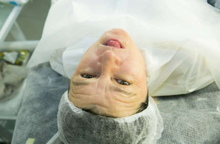 A visit to the beautician. Procedure-carboxytherapy. The doctor removes the rejuvenating mask from the patient's face.