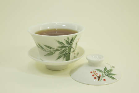 Chinese tea. Golden Eyebrow Tea. Tea in a beautiful traditional oriental cup with saucer. Isolated in a white bowl on a white background. Foto de archivo