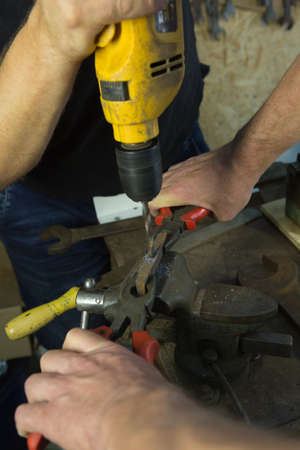 Working with a vise and drill. The master uses a drill. Portrait of a master at work. The young man works with an assistant. Banco de Imagens