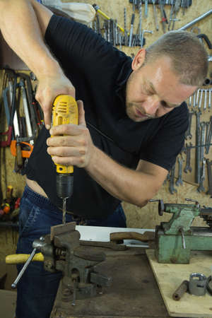 Working with a vise and drill. The master uses a drill. Portrait of a master at work.