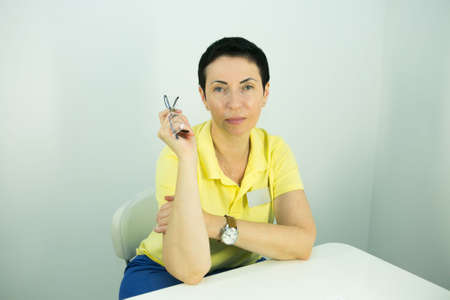 Doctor is a beautician. Portrait of a middle-aged woman. The doctor tells the patient about the need for facial skin care.