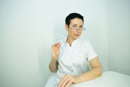 Dr. cometologist. A woman prepares a syringe with medication to correct wrinkles.