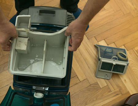 The process of cleaning a room with a vacuum cleaner with an aquafilter. Filling the tank with clean water and placing it in the body of the vacuum cleaner before starting cleaning