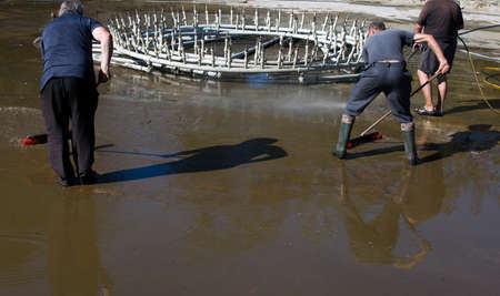 Cleaning of city fountains before winter. Workers clean the mud that has settled over the season.