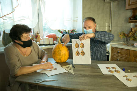 How to make Jack O'Lantern at home? A middle aged man and woman are doing Jack O'Lantern in the kitchen. There are masks on people's faces. The couple argue about how to cut the pumpkin properly.