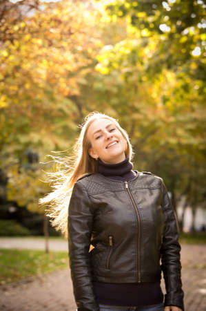 Beautiful young woman on a background of autumn trees. Emotion concept. Walk in the autumn park. Backlight shooting.