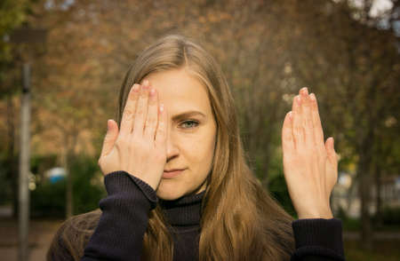 Beautiful young woman on a background of autumn trees. Emotion concept. The girl covers her face with her hand.