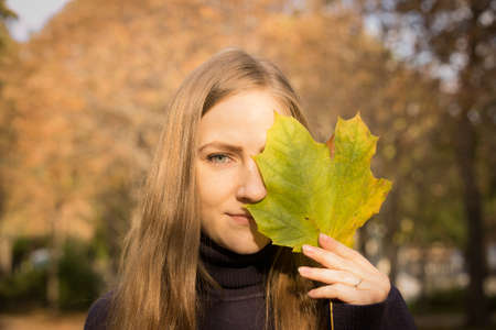 Beautiful young woman on a background of autumn trees. Emotion concept. The girl holds a maple leaf in her hand and covers one eye with the leaf.