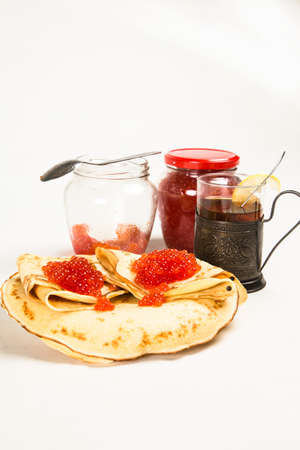 Traditional Russian pancakes with red caviar. In the background is a jar with red salmon caviar and a glass in a glass holder with black tea.