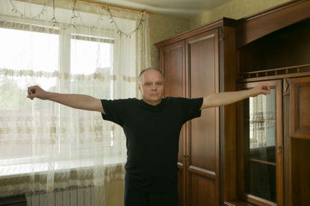 Morning exercises. An aged man is engaged in gymnastics at home. All fitness centers are closed during the quarantine period.