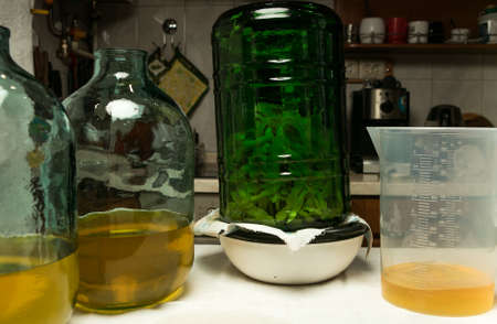 The filtration of the alcoholic infusion on lemon zest ends. Two ten-liter bottles are filled with the right amount of alcohol infused with lemon zest.