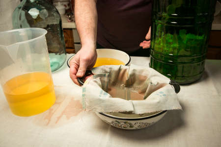 The man drains and strains the alcohol infused with lemon peel. The master measures the required volume of liquid for mixing with the sugar syrup.