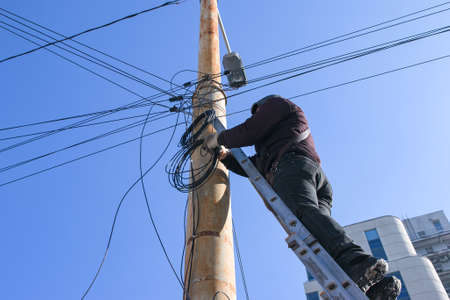 The process of repairing electrical connections. A working electrician repairs an electrical line at a high altitude.