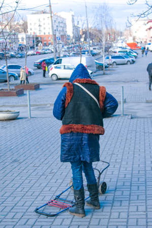 Dnepropetrovsk, Ukraine - February 28, 2021: A homeless and poorly dressed woman walks through the city. Selective focus, street photo, urban poverty.