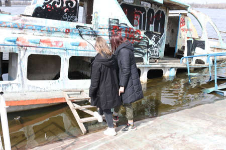 Dnepropetrovsk, Ukraine - 08.04.2021: Old rusty sunken ship in the water on the territory of the river port. Two teenage girls are trying to get inside a half-flooded boat.