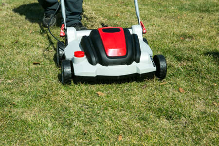 Aeration with a scarifier. Using a scarifier in the garden to improving quality of the lawn in spring. A worker man, Gardener Operating Soil Aeration Machine on Grass Lawn.