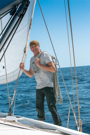 A man on board a sailing yacht at sea. Yachting. Active lifestyle concept.