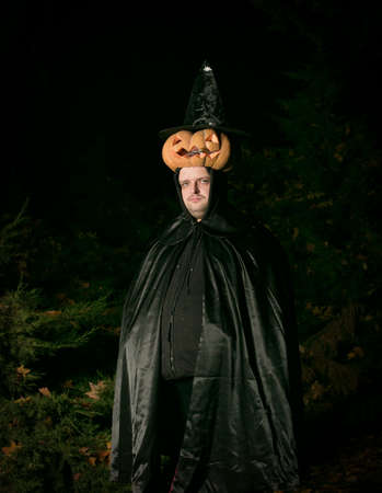 Portrait of a man with a pumpkin on his head. The guy in the Dracula costume.