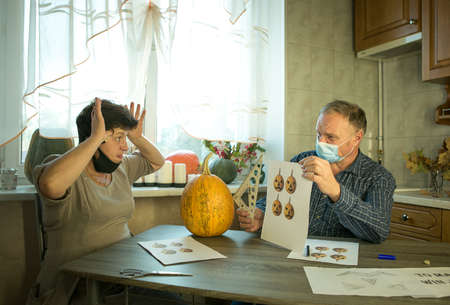 How to make Jack O'Lantern at home? A middle aged man and woman are doing Jack O'Lantern in the kitchen. There are medical masks on people's faces. The couple argue about how to cut the pumpkin properly.