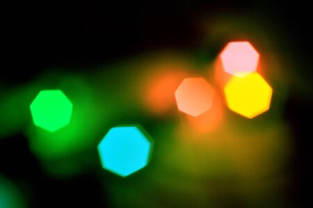Glowing and festive colored light circles created from in camera and lens bokeh. Christmas fairy lights defocused giving a blurred effect. Background for design.