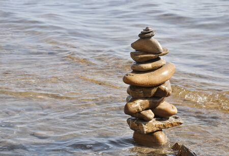 The stones are balanced on the sea. Stone towers on a sunny day. Banco de Imagens