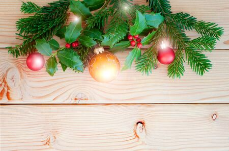 Christmas border on wooden background. Branch of fir and holly