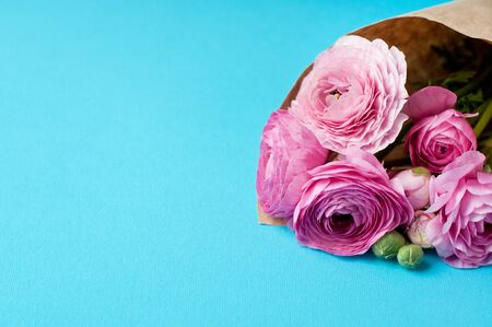 A bouquet of pink ranunculus flowers in craft wrapping paper on a blue background. Top view, copy space. Concept Mother's Day, Family Day, Valentine's Day