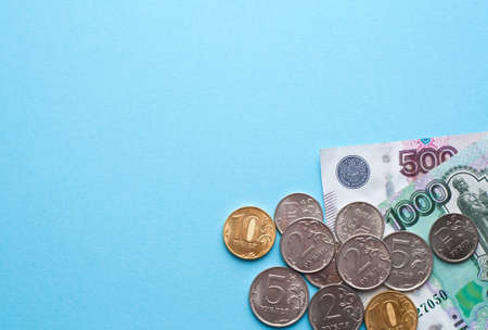 Russian rubles on a blue background. Thousand notes and various coins. Place for text.