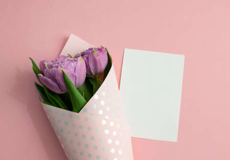 Bouquet of lilac tulips wrapped in wrapping paper. A white sheet of paper lies on pink paper. Top view, copy space. Concept for Mother's Day, Family Day, Valentine's Day