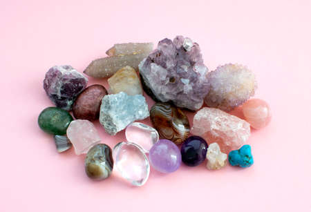Tumbled and rough gemstones and crystals of various colors. Amethyst, rose quartz, agate, apatite, aventurine, olivine, turquoise, aquamarine, rock crystal. Selective focus.