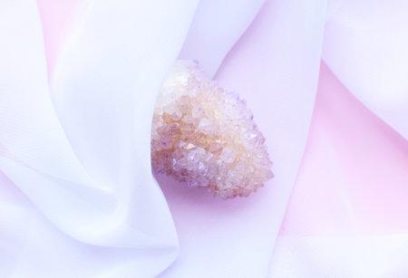 Beautiful pink crystals of amethyst quartz on white transparent fabric. Cactus quartz, known as spirit quartz.