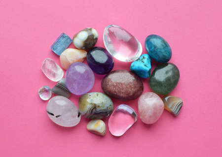 Tumbled and rough gemstones and crystals of various colors. Amethyst, rose quartz, agate, apatite, aventurine, olivine, turquoise on pink background.