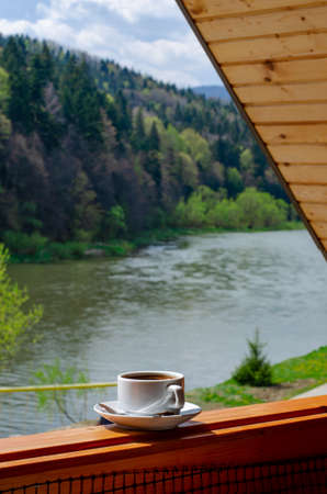 Cup of coffee with the view on the mountains and river, vertical size