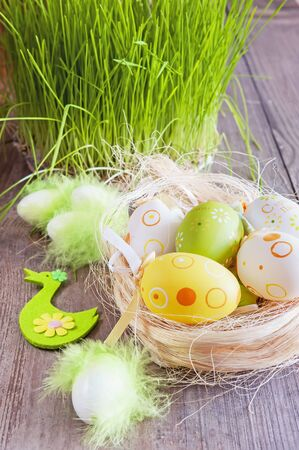 colorful Easter eggs lying on the table next to the green fresh grass Stock Photo