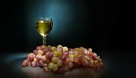 Bunch of grapes near a glass of white wine standing on background with reflection