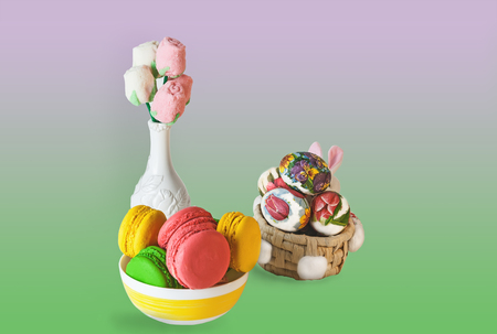 Easter colorful sweet macaroon marshmallow flowers in a white vase, colorful eggs in a basket on a Colored background