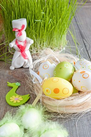 Easter eggs of different colors lying on the table next to the green of fresh grass and the white rabbit