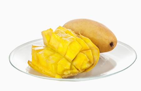 chopped mango half crosswise, lying on a glass plate on the background of a whole mango
